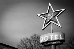Russell Viers taking pictures of old motel and other neon signs on colfax avenue in denver, co on kooky's road trip with a nikon f4